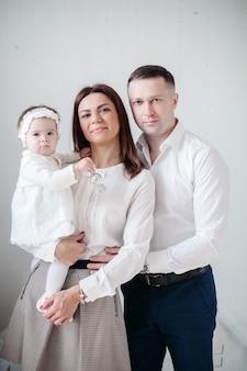 Studio portret van prachtige familie met babymeisje gekleed als een engel lachend aan de voorkant