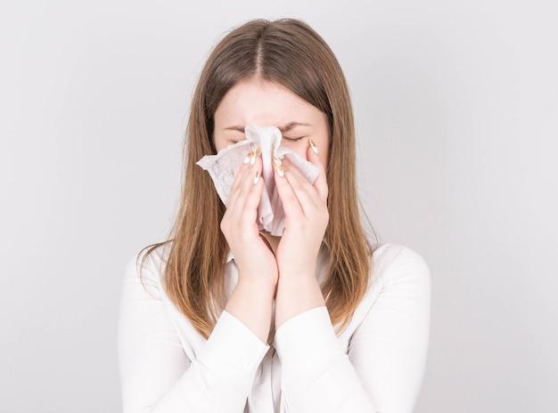 Studio portret van schattige ongezonde blanke vrouw met papieren servet niezen, ervaringen allergiesymptomen
