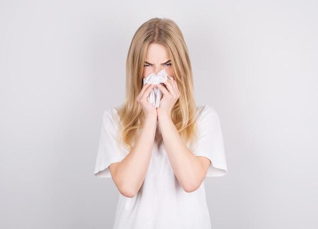 Studio portret van schattige ongezonde blanke vrouw met papieren servet niezen vanwege allergie, griep of verkoudheid