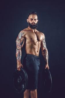 Studio portret van shirtless getatoeëerd bebaarde man houdt halter op zwarte muur.