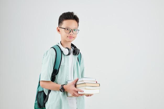 Studio portret van slimme schooljongen met rugzak en stapel boeken kijken