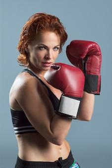 Studio portret van sportieve rijpe vrouw in bokshandschoenen op grijs