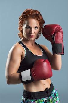 Studio portret van sportieve rijpe vrouw in bokshandschoenen op grijze ruimte, atletische roodharige serieuze vrouw
