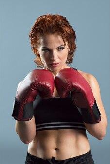 Studio portret van sportieve rijpe vrouw in bokshandschoenen