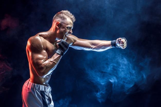 Studio portret van vechten gespierde man in rook op donker