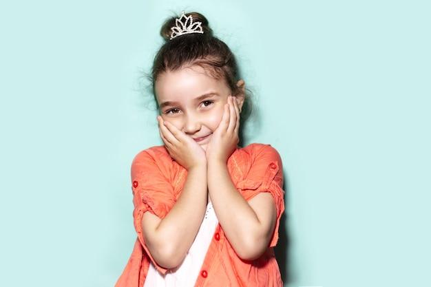 Studio portret van verlegen klein kind meisje, met palmen op de wangen
