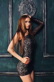Studio portret van verleidelijk slank meisje, gekleed in sexy zwarte mini jurk poseren over vintage houten paneel muur.