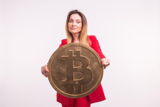 Studio portret van zakelijke dame in rood pak met bitcoin op handen.
