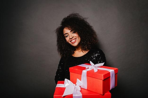 Studio portret van zalige krullende vrouw met cadeautjes