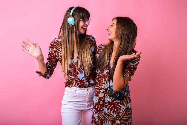 Studio positief beeld van tho mooie beste vrienden vrouw dansen en plezier maken op feestje, schattige verrast emoties, stijlvolle kleur bijpassende kleding, grote koptelefoon en vintage camera.