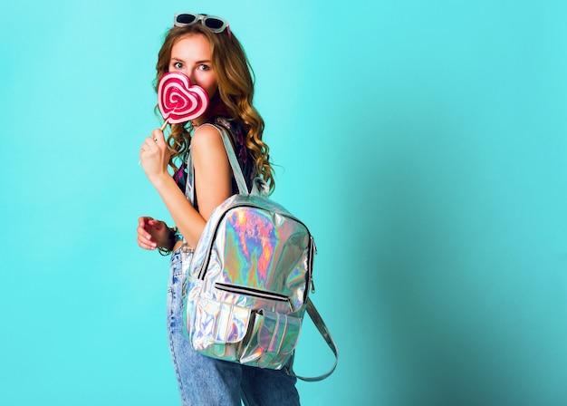 Studio positief portret van het jonge sexy grappige manier gekke vrouw stellen op blauwe muurachtergrond in de uitrusting van de de zomerstijl met roze lolly die drukbovenkant, neonrugzak en leuke glazen dragen.