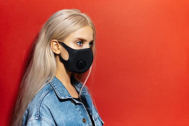Studio profiel portret van jong blond meisje, dragen respiratoire gezichtsmasker van zwarte kleur, tegen coronavirus. achtergrond van rode kleur met exemplaarruimte.