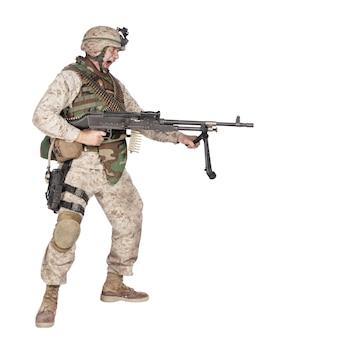 Studio shoot van schreeuwende leger soldaat met machinegeweer, marine corps machine gunner in camo uniform met munitie riem op kogelvrije vesten, staande, schreeuwen en schieten vanuit de taille, geïsoleerd op witte achtergrond