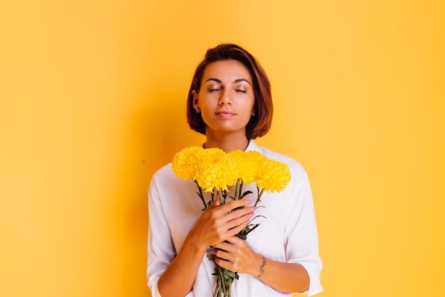 Studio shot op gele achtergrond gelukkig blanke vrouw kort haar dragen casual kleding wit overhemd en denim broek bedrijf boeket gele asters