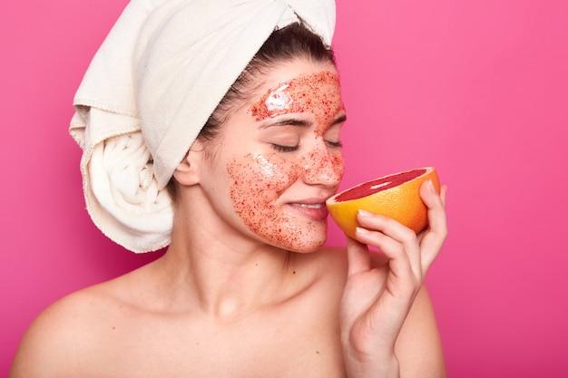 Studio shot van aangenaam ogende jonge europese vrouw ruiken grapefruit