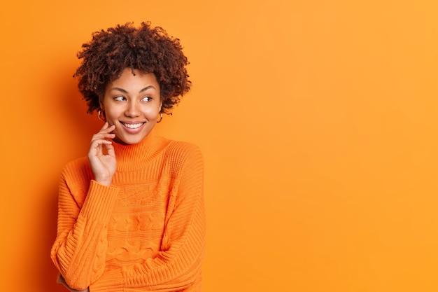 Studio shot van aangenaam uitziende doordachte lachende etnische vrouw geconcentreerd opzij drukt positieve emoties draagt casual trui staat tegen levendige oranje muur