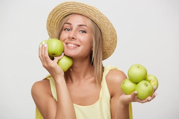 Studio shot van aangenaam uitziende jonge aantrekkelijke blonde dame met casual kapsel poseren op witte achtergrond met groene appels in opgeheven handen en gelukkig lachend