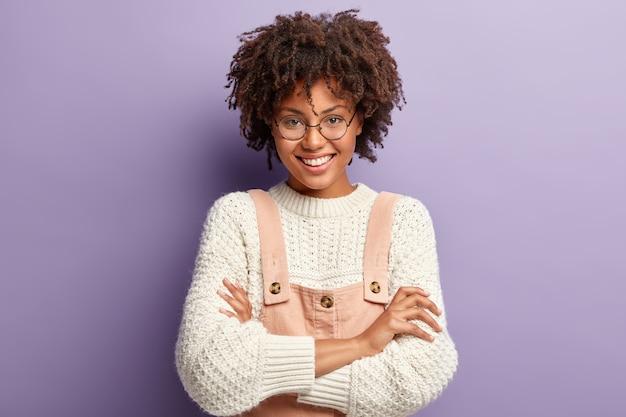 Studio shot van aangenaam uitziende vriendelijke vrouw met afro kapsel, geniet van het leven, lacht zachtjes