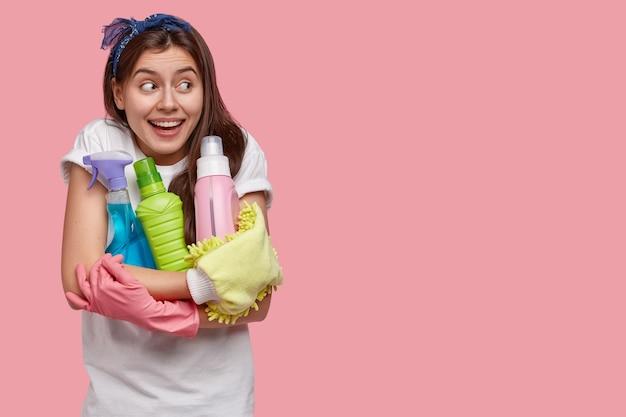 Studio shot van aangenaam uitziende vrolijke vrouw geconcentreerd opzij, draagt veel flessen afwasmiddel, draagt beschermende rubberen handschoenen