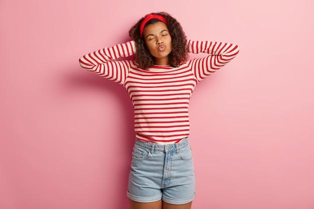 Studio shot van aangename tiener meisje met krullend haar poseren in gestreepte rode trui