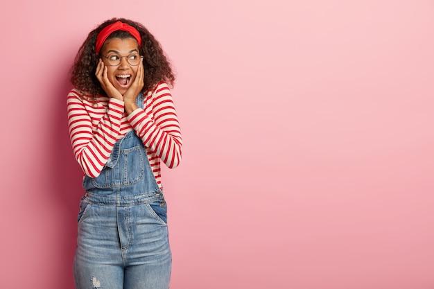 Studio shot van aangename tiener poseren in overall met krullend haar