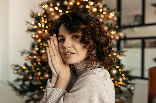 Studio shot van aantrekkelijke donkerharige vrouw met golvend haar poseren van kerstboom, nieuwjaar, kerstmis