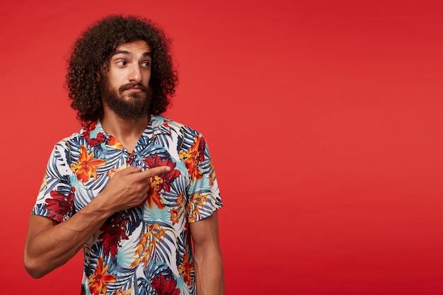 Studio shot van aantrekkelijke jonge brunette gekrulde man met baard vrijetijdskleding dragen terwijl staande op rode achtergrond, opzij tonen met opgeheven wijsvinger en rimpelend voorhoofd met gevouwen lippen
