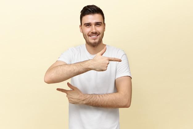 Studio shot van aantrekkelijke jonge donkerharige man in wit t-shirt camera kijken met een brede glimlach, wijsvinger wijzend in tegengestelde richtingen, probeert je te verwarren, manier tonen
