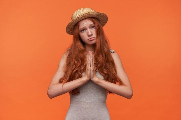 Studio shot van aantrekkelijke roodharige vrouw met lang golvend haar camera kijken met droevig gezicht, samen gevouwen handen opheffen en azen voor beter, geïsoleerd op oranje achtergrond