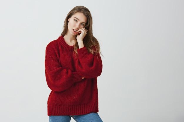 Studio shot van aantrekkelijke stijlvolle vrouwelijke model poseren in trendy trui terwijl het bijten van de vingernagel en het kantelen van hoofd, na te denken over iets of uit elkaar. meisje neemt moeilijke beslissing