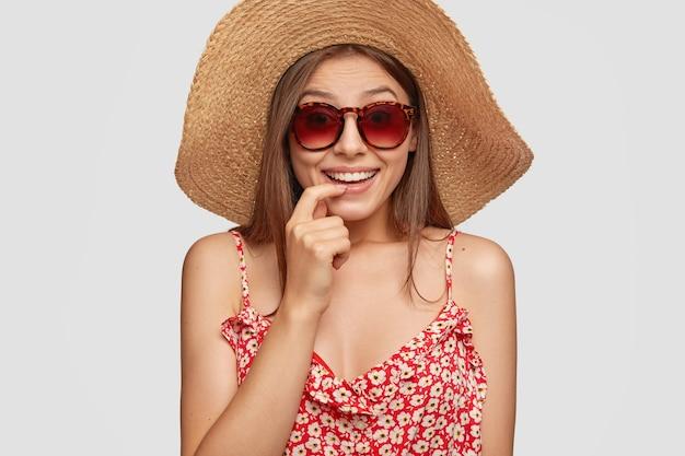Studio shot van aantrekkelijke vrouw heeft zomervakantie, lacht positief en houdt vinger in de buurt van mond