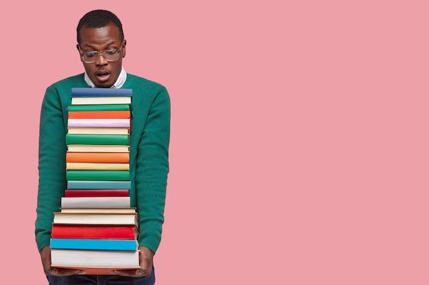 Studio shot van angstige donkere huid jonge man kijkt verrassend naar stapel boeken