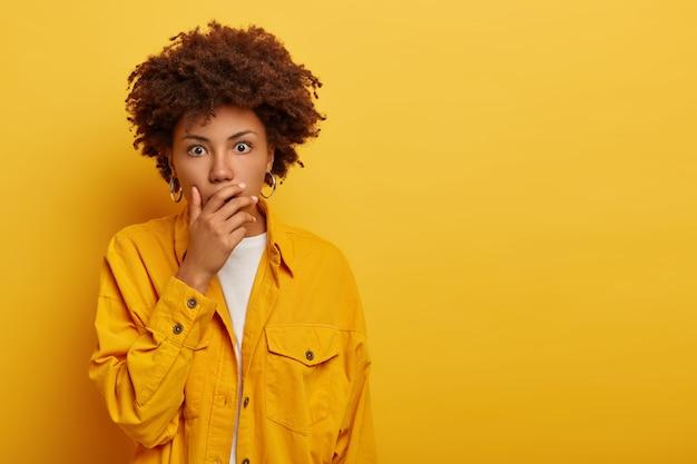 Studio shot van bang gekrulde vrouw bedekt mond met schrik, bang door angstaanjagend ding, gekleed in modieuze gele jas, kan ogen niet geloven, staat binnen, lege kopie ruimte voor advertentie