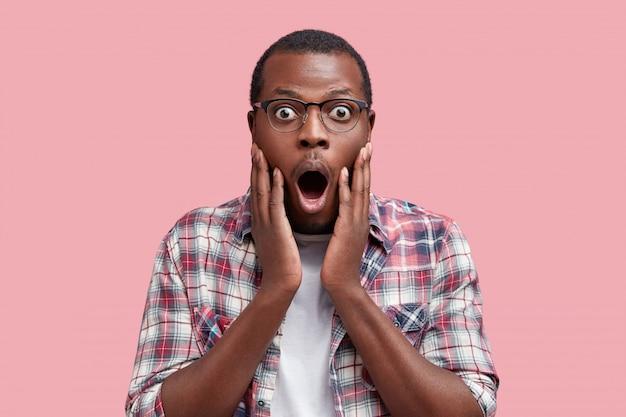 Studio shot van bange doodsbange afrikaanse klant met een donkere huid geschokt door de prijzen in de winkel, zonder geld om iets te kopen, geïsoleerd over roze