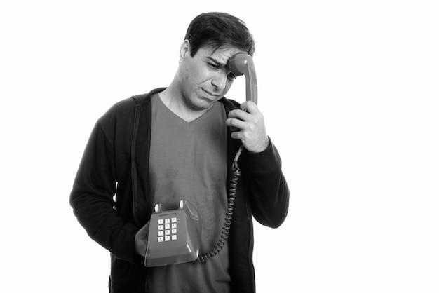 Studio shot van beklemtoonde jonge perzische man die moe kijkt terwijl hij een oude telefoon op het hoofd houdt geïsoleerd