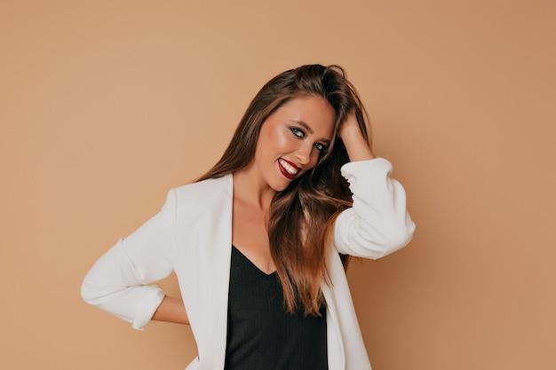 Studio shot van blije vrouw in witte jas is poseren op beige achtergrond