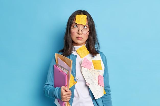 Studio shot van brunette jonge aziatische schoolmeisje bestudeert wiskunde hierboven geconcentreerd op voorhoofd met sticker houdt mappen