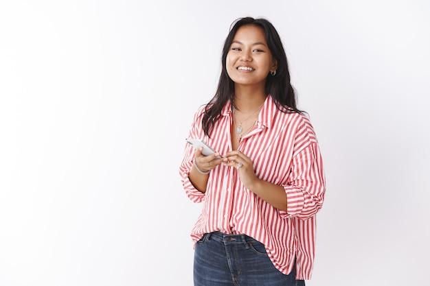Studio shot van charmante gelukkige jonge vietnamese vrouw in gestreepte blouse met smartphone grijnzend naar camera tevreden en vrolijk blij met goed nieuws gelezen via internet in mobiele telefoon