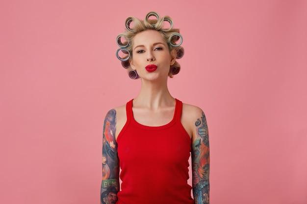Studio shot van charmante jonge blonde getatoeëerde dame kapsel maken en haar rode lippen in lucht kus vouwen terwijl staande op roze achtergrond in rood shirt met handen naar beneden