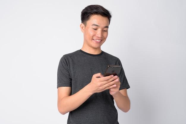 Studio shot van de jonge knappe aziatische man tegen een witte achtergrond