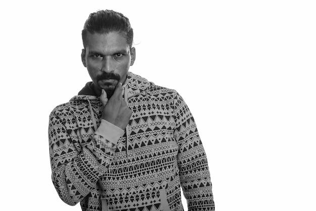 Studio shot van de jonge knappe bebaarde indiase man met hoodie tegen wit in zwart-wit