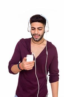Studio shot van de jonge knappe indiase man met behulp van mobiele telefoon