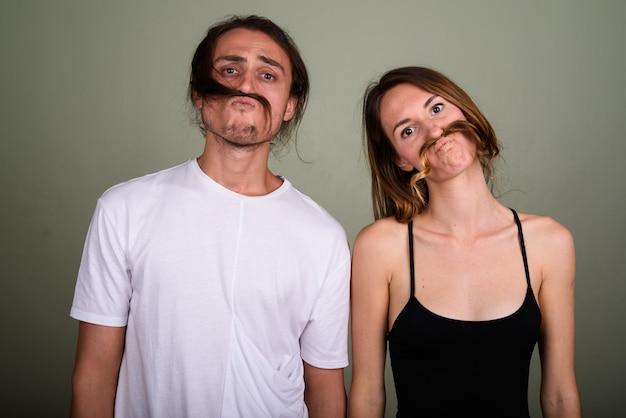 Studio shot van de jonge knappe man en jonge mooie vrouw samen tegen een gekleurde achtergrond