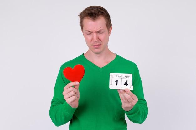 Studio shot van de jonge knappe man klaar voor valentijnsdag tegen witte achtergrond