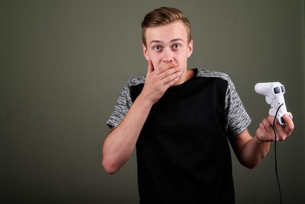 Studio shot van de jonge knappe man met blond haar tegen een gekleurde achtergrond