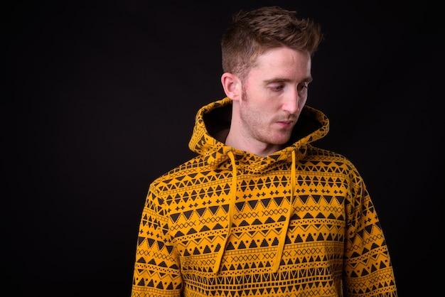 Studio shot van de jonge knappe man met hoodie tegen zwarte achtergrond