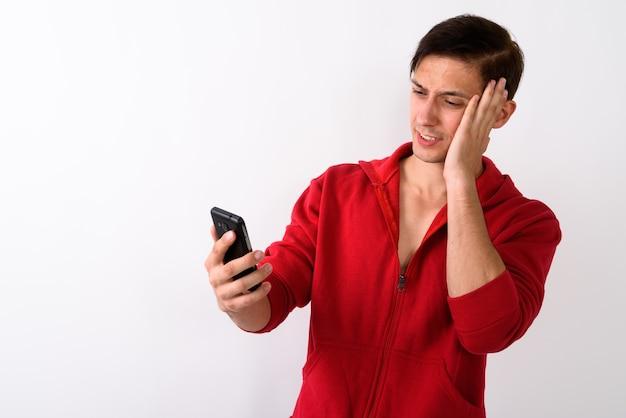 Studio shot van de jonge knappe man met hoofdpijn tijdens het gebruik van mo