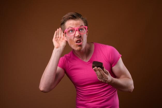 Studio shot van de jonge knappe man met roze shirt met bijpassende roze bril terwijl het hebben van chocoladetaart tegen bruine achtergrond