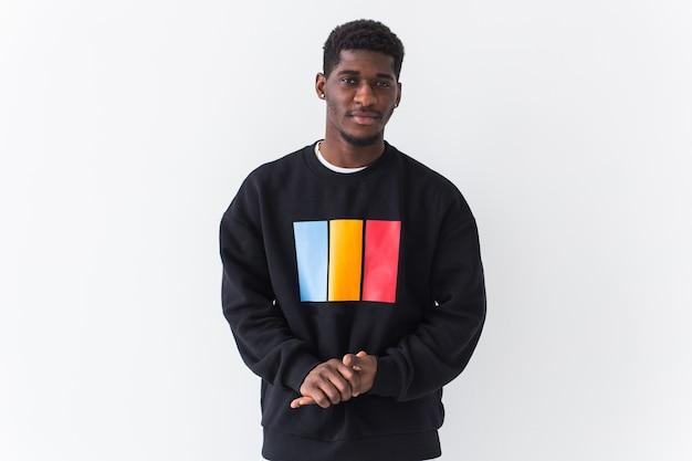 Studio shot van de jonge knappe man met sweatshirt tegen witte muur