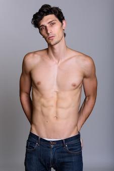 Studio shot van de jonge knappe man shirtless met handen op rug